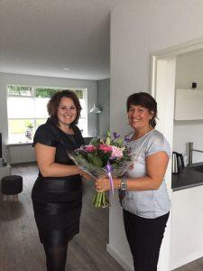 Ilse Hilbink, links op de foto, ontvangt bloemen van Janet Kroezen
